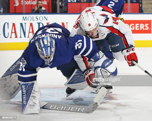 Justin Williams of the Washington Capitals bumps into goalie Frederik Andersen of the Toronto Maple Leafs in Game Three of the Eastern Conference...