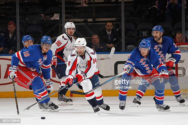 Justin Williams of the Washington Capitals skates with the puck against Marc Staal and Oscar Lindberg of the New York Rangers at Madison Square...