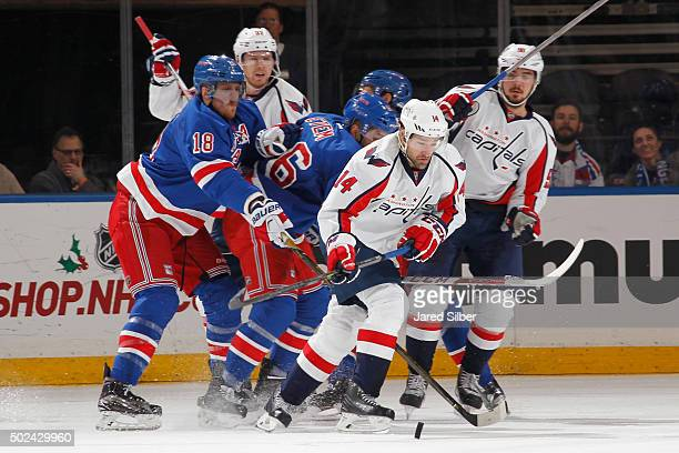 Justin Williams of the Washington Capitals skates with the puck against Marc Staal and Emerson Etem of the New York Rangers at Madison Square Garden...