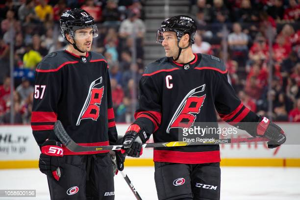 Justin Williams talks with teammate Trevor van Riemsdyk of the Carolina Hurricanes on a play stoppage during an NHL game against the Detroit Red...