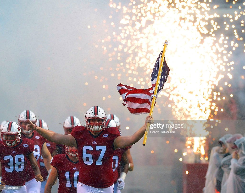 Justin Witt #67 of the North Carolina State Wolfpack leads his team onto the field during the game against the Notre Dame Fighting Irish at Carter Finley Stadium on October 8, 2016 in Raleigh, North Carolina.