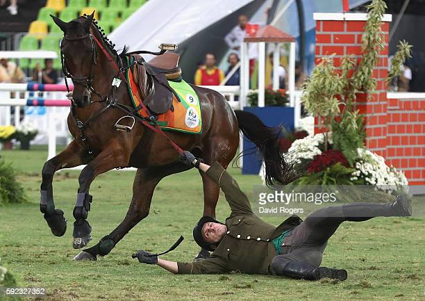 Justinas Kinderis of Lithuania falls during the show jumping round of Modern Pentathlon on Day 15 of the Rio 2016 Olympic Games at Deodoro Stadium on...