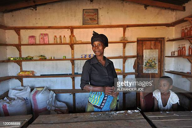 Justine Gerardy Gladys Josephat poses with her children in her small shop that she got from a micro finance loan run outside Lilongwe on July 14 2011...