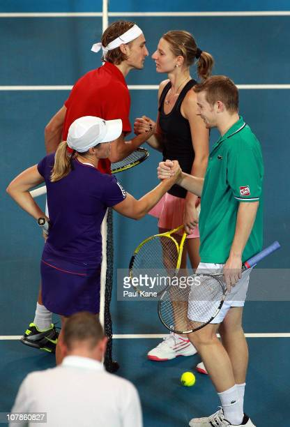 Justine Henin and Ruben Bemelmans of Belgium shake hands with Andrey Golubev and Sesil Karatantcheva of Kazakhstan after winning their mixed doubles...
