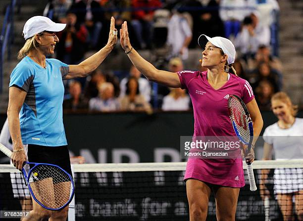 Justine Henin of Belgium and Martina Navratilova high five suring their doubles macth against Steffi Graf and Lindsay Davenport during Hit for Haiti...