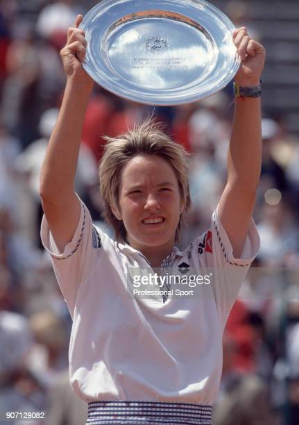Justine Henin of Belgium lifts the trophy after defeating Cara Black of Zimbabwe in the Junior Girls' Final of the French Open Tennis Championships...