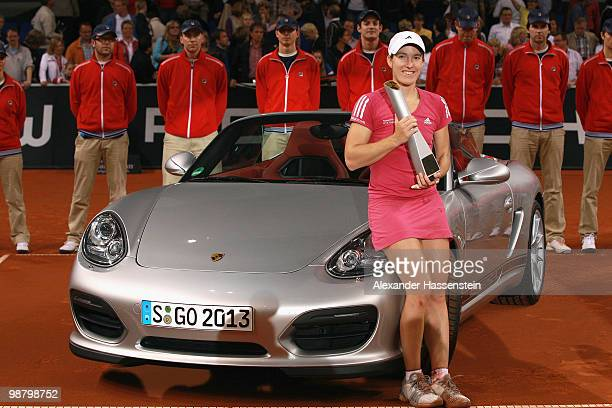 Justine Henin of Belgium poses with the winners present, a Porsche Boxter Spyder after winning her final match against Samantha Stosur of Australia...