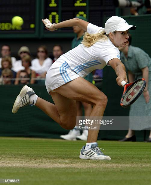 Justine Henin-Hardenne lunges for a shot during her lost game against Serena Williams, 6-3, 6-2