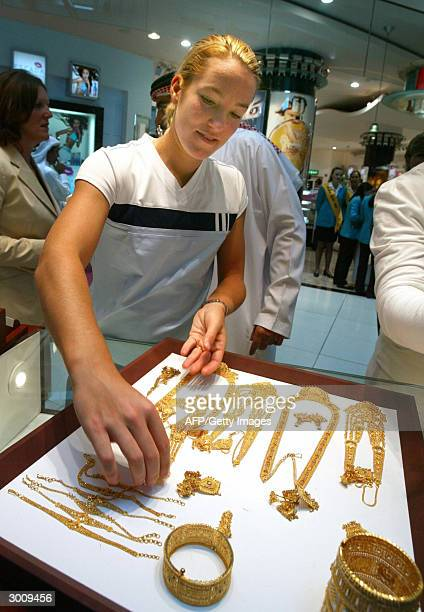 Justine HeninHardenne of Belgium the world number one tries on jewellery during a visit to a gold shop in Dubai international airport 24 February...