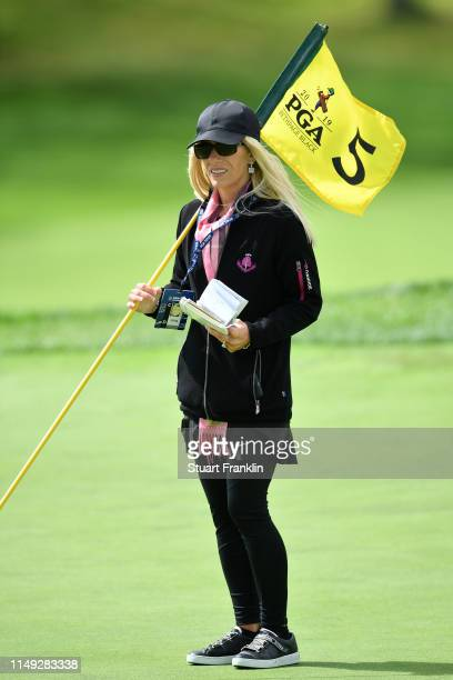 Justine Karain wife of Patrick Reed holds the flag on the fifth green during a practice round prior to the 2019 PGA Championship at the Bethpage...