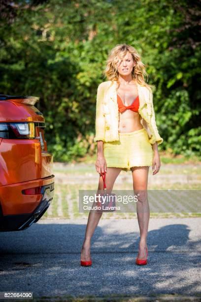 Justine Mattera wearing a Edward Achour yellow suit Elisabetta Franchi bag Paladini Lingerie orange bikini and Giovanni Fabiani shoes is seen near of...