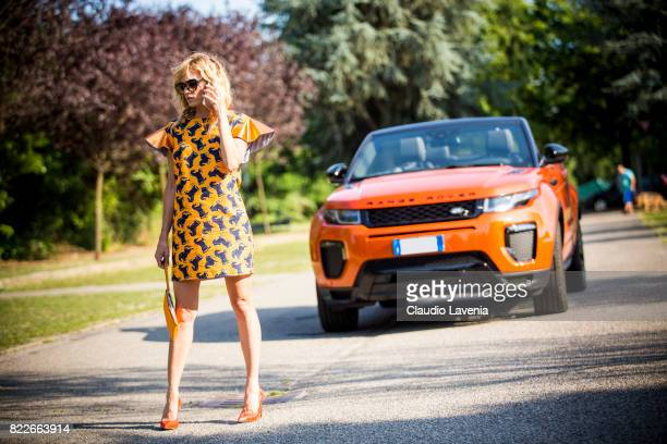 Justine Mattera wearing a Mauro Gasperi orange dress Alef orange bag Dsquared2 sunglasses and Giovanni Fabiani shoes is seen ahead of her Range Rover...
