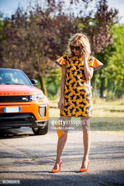 Justine Mattera wearing a Mauro Gasperi orange dress Alef orange bag Dsquared2 sunglasses and Giovanni Fabiani shoes is seen ahead of her Range Rover...