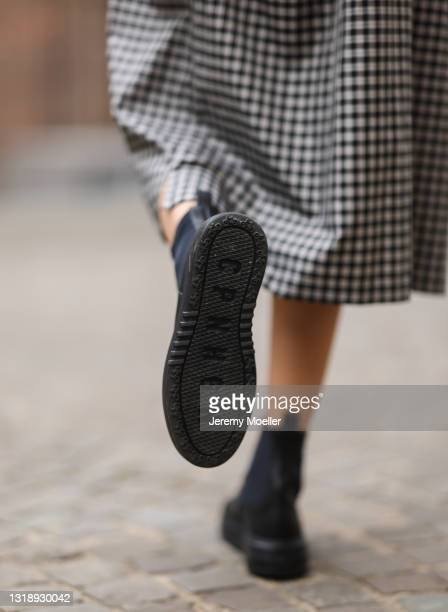 Justine Schlütter wearing checked grey and black Balenciaga dress and black Copenhagen Studios boots on May 11, 2021 in Cologne, Germany.