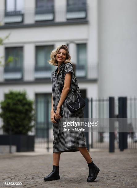 Justine Schlütter wearing checked grey and black Balenciaga dress, black Prada nylon bag and black Copenhagen Studios boots on May 11, 2021 in...