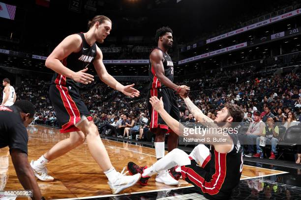 Justise Winslow and Kelly Olynyk help up Tyler Johnson of the Miami Heat during the game against the Brooklyn Nets during a preseason game on October...