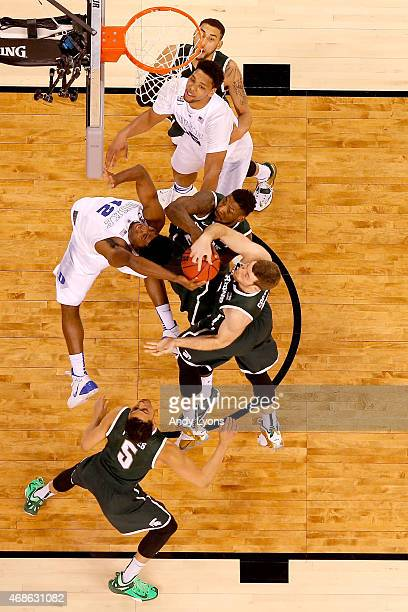 Justise Winslow of the Duke Blue Devils goes up with the ball against Matt Costello and Branden Dawson of the Michigan State Spartans in the first...