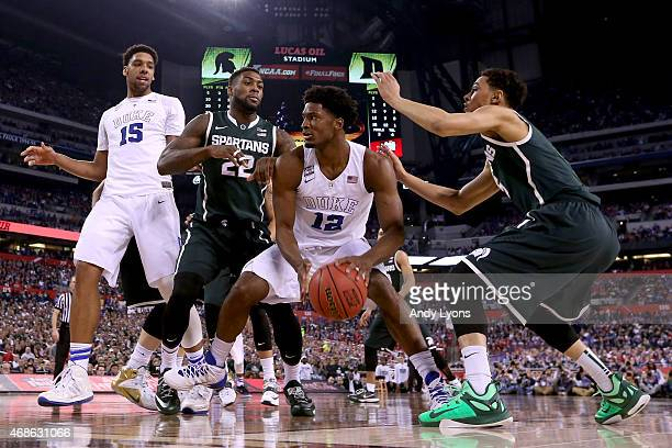 Justise Winslow of the Duke Blue Devils handles the ball against Branden Dawson and Bryn Forbes of the Michigan State Spartans in the second half...