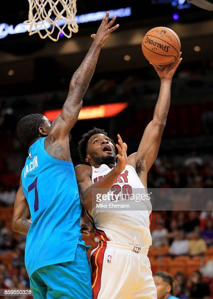 Justise Winslow of the Miami Heat drives on Dwayne Bacon of the Charlotte Hornets during a preseason game at American Airlines Arena on October 9...