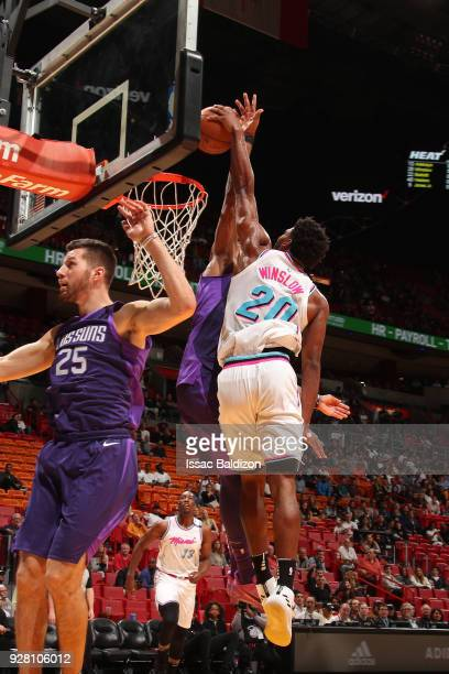 Justise Winslow of the Miami Heat dunks the ball while guarded by Marquese Chriss of the Phoenix Suns on March 5 2018 at American Airlines Arena in...