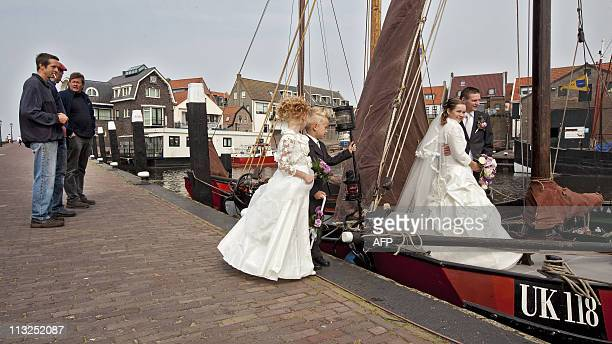 A justmarried couple poses on a boat in the harbor of Urk on April 28 2011 located on the Noordoostpolder a polder landscape in the North of the...