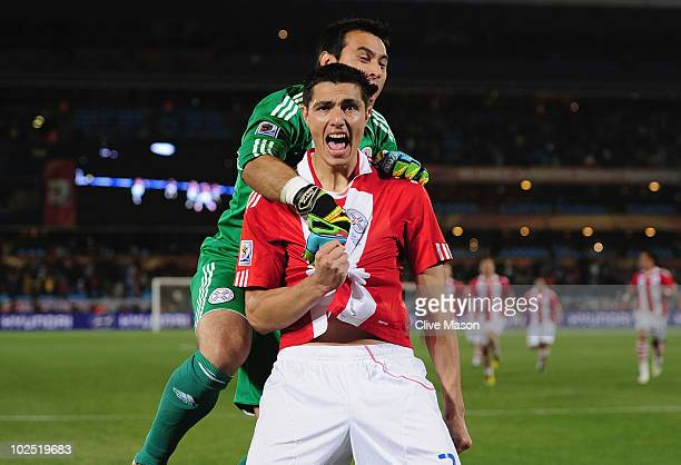 Justo Villar celebrates with Oscar Cardozo of Paraguay after scoring his penalty to win his team a penalty shootout during the 2010 FIFA World Cup...