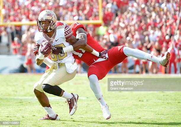 Juston Burris of the North Carolina State Wolfpack tackles Rashad Greene of the Florida State Seminoles during their game at CarterFinley Stadium on...