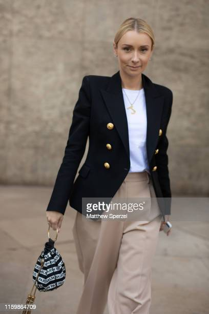 Justyna Czerniak is seen on the street during Paris Fashion Week Haute Couture wearing navy blazer with khaki pants and pink sneakers on July 03 2019...