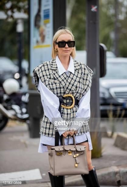 Justyna Czerniak seen wearing sleeveless jacket, white button shirt, Bottega Veneta belt, Hermes bag, black boots outside Hermes during Paris Fashion...