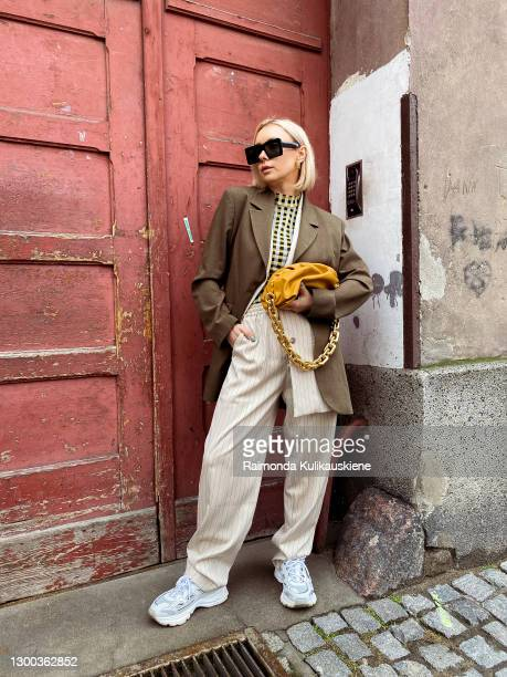 Justyna Czerniak wearing Baum und Pferdgarten top, Munthe trousers and vest, Axel Arigato shoes and Bottega Veneta bag poses during an online street...