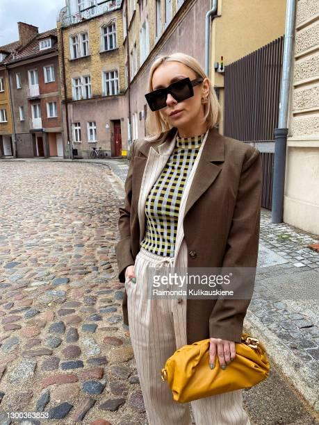 Justyna Czerniak wearing Baum und Pferdgarten top, Munthe trousers and vest, Axel Arigato shoes and Bottega Veneta bag poses during an online street...