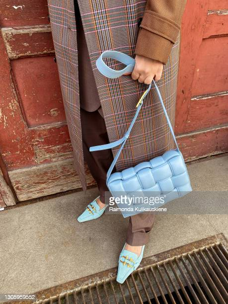 Justyna Czerniak wearing Marine Serre top, InWear pants and blazer, Birgitte Herskind coat, Bottega Veneta bag and shoes poses during an online...