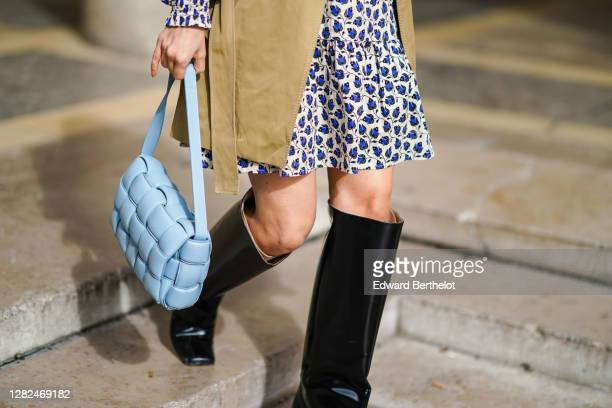 Justyna Czerniak wears a beige trench coat, a blue and white floral print pleated dress, a blue quilted Bottega Veneta bag, black leather high boots,...