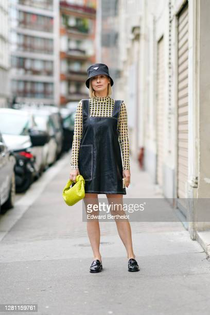 Justyna Czerniak wears a black Prada bob hat, a black dress, a yellow and black checkered top, a yellow woven leather bag from Bottega Veneta, black...