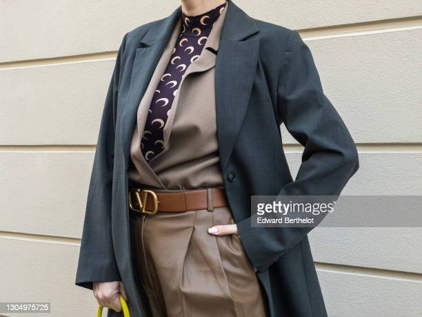 Justyna Czerniak wears a brown vest from Munthe, a turtleneck top with printed moon logos from Marine Serre, a gray oversized blazer jacket from...