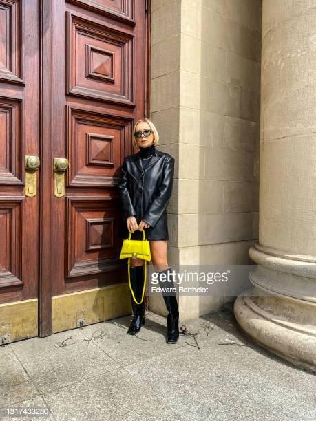 Justyna Czerniak wears a Hidemi black leather blazer jacket, a golden necklace, a black turtleneck pullover, a yellow Balenciaga bag, Bottega Veneta...