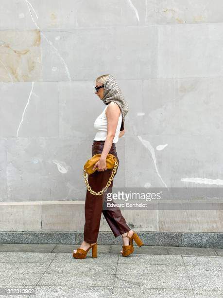 Justyna Czerniak wears a white tank top from In Wear, brow leather crocodile pattern pants from Samsoe Samsoe, a pale brown pouch leather bag with a...