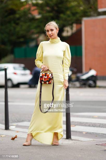 Justyna Czerniak wears earrings a light yellow hineck puff sleeves asymmetric long dress a Chloe orange brown and white bag mesh heels outside Ann...