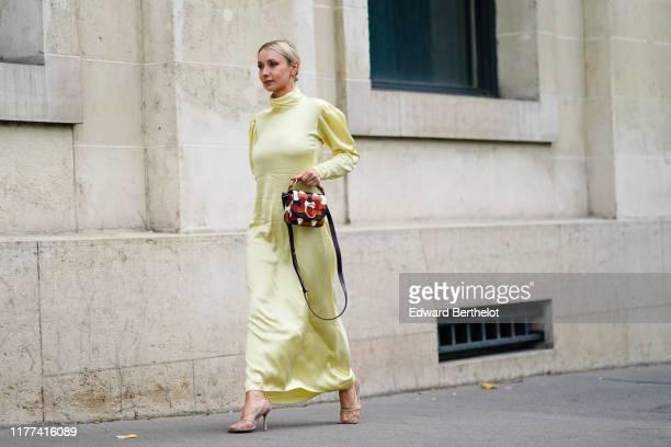 Justyna Czerniak wears earrings, a light yellow hi-neck puff sleeves asymmetric long dress, a Chloe orange, brown and white bag, mesh heels, outside...