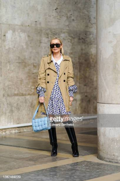 Justyna Czerniak wears sunglasses, a beige trench coat, a blue and white floral print pleated dress with white collar, a blue quilted Bottega Veneta...