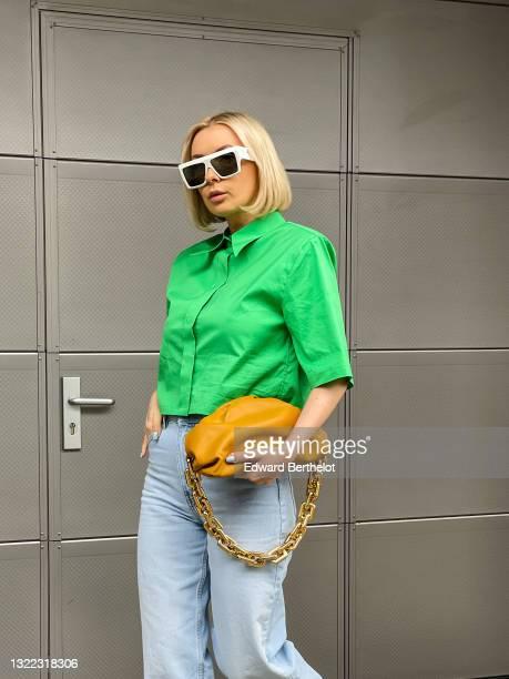 Justyna Czerniak wears sunglasses, a green shirt, a brown leather golden chain pouch Bottega Veneta bag, blue long ripped denim jeans pants, during...
