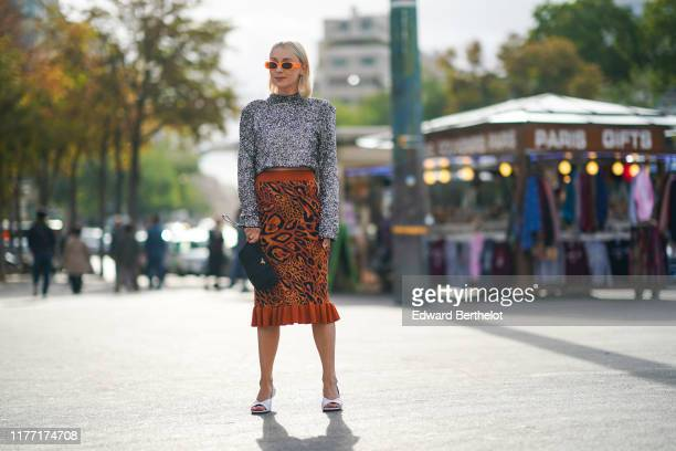 Justyna Czerniak wears sunglasses a hineck glittering grey top a tangerine and black animal print skirt white sandals with sculpted heels a black...