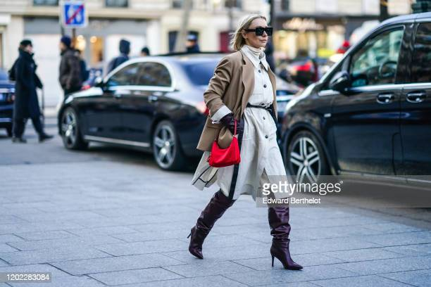 Justyna Czerniak wears sunglasses, a light brown oversized jacket, a white turtleneck, a gray dress with buttons, a red bag, purple leather high...