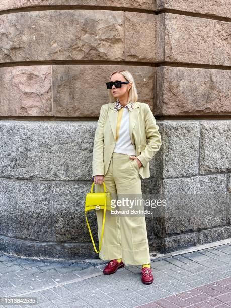 Justyna Czerniak wears sunglasses, a pastel colored beige / yellow blazer jacket from Baum und Pferdgarten, suit flared pants from Baum und...