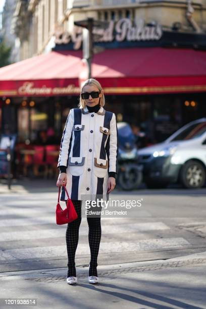Justyna Czerniak wears sunglasses a red bag from Prada a striped long coat tights white pointy shoes outside Chanel during Paris Fashion Week Haute...
