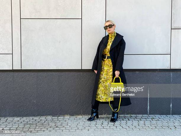 Justyna Czerniak wears sunglasses, earrings, a black long quilted/padded coat from Baum, a yellow floral print dress from Baum, a Bottega Veneta belt...