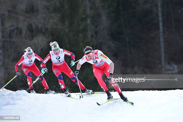 Justyna Kowalczyk of Poland Norway's Therese Johaug and Finland's Krista Lahteenmaki compete during the women's 10 km Classic mass start race 6 of...