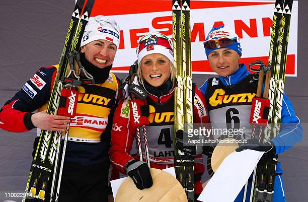 Justyna Kowalczyk of Poland Therese Johaug of Norway and Arianna Follis of Italy pose on the podium after the women's 5km pursuit of the FIS World...