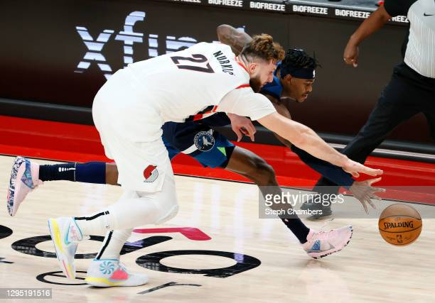 Jusuf Nurkic of the Portland Trail Blazers and Jarred Vanderbilt of the Minnesota Timberwolves reach for a loose ball during the third quarter at...