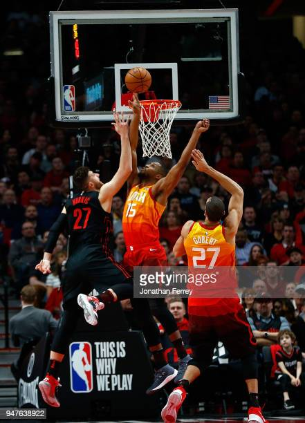 Jusuf Nurkic of the Portland Trail Blazers lays up the ball against Rudy Gobert and Derrick Evans of the Utah Jazz at Moda Center on April 11 2018 in...